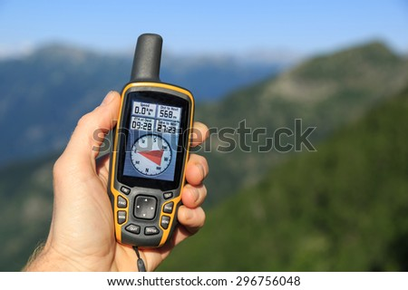 Hand held GPS used for navigation in the mountains. - stock photo
