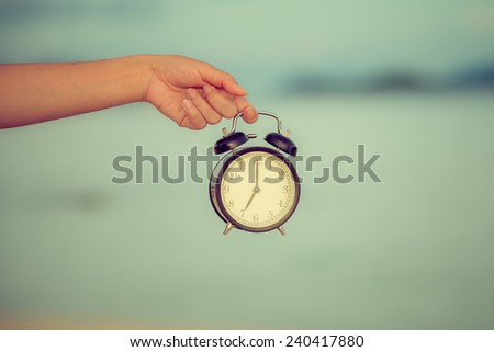 Hand hold alarm clock with sea background. Retro filter. - stock photo