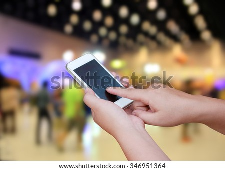 hand hold and touch screen smart phone, on blurred photo of department store shopping mall center and people background - stock photo