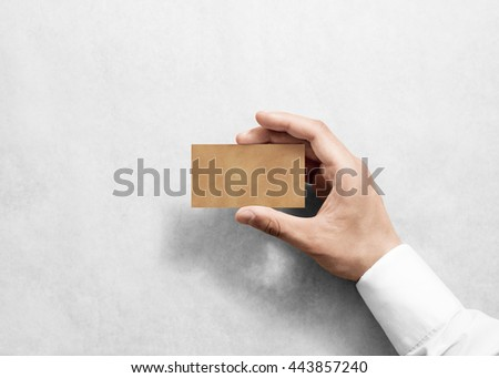 Hand hold blank plain craft business card design mockup. Brown calling card mock up template holding arm. Visit pasteboard kraft paper display front. Small offset texture card print. Logo branding - stock photo