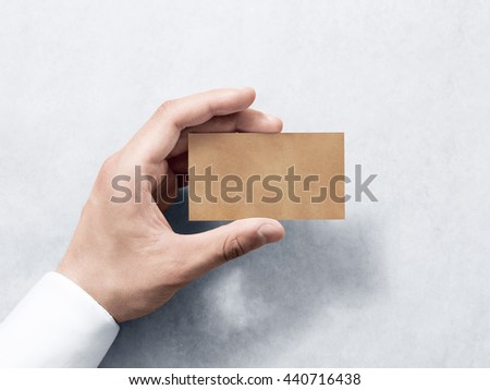 Hand hold blank plain kraft business card design mockup. Clear calling card mock up template holding arm. Visit pasteboard craft paper display front. Small offset texture card print. Business identity - stock photo