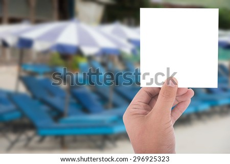 hand hold blank square paper over blur beach background