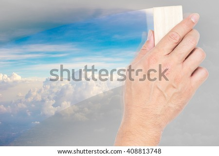 hand hold board eraser with nature background, help clean air pollution concept. - stock photo