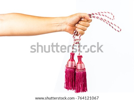 Hand hold Colorful Curtain rope on white background