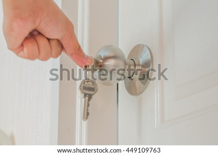 Hand hold door knob and open the white door with private key as locksmith concept.
