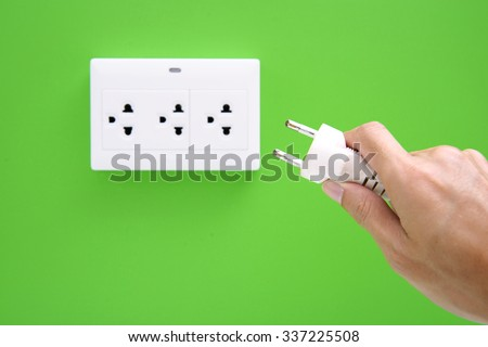Hand hold electric power plug and inserting into power wall socket - stock photo