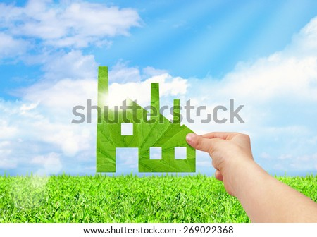 Hand hold factory iconon field and blue sky background, Eco green factory concept - stock photo