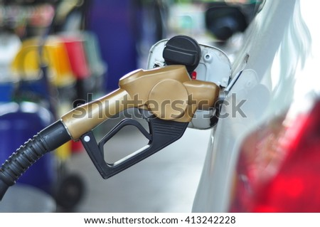 Hand hold fuel nozzle to add fuel in car at filling station. - stock photo