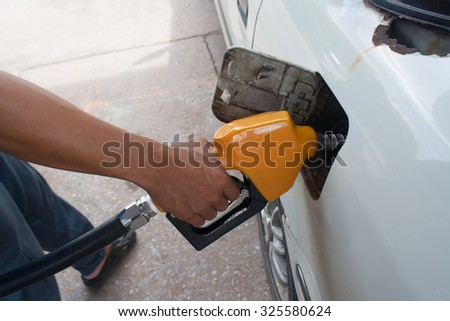 Hand hold Fuel nozzle to add fuel in car at filling station. Focus on the handle arm.