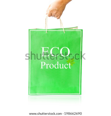 Hand hold green paper shopping bag on reflect white floor. Eco Product - stock photo
