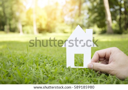 Hand hold house against green field (estate, real, house)
