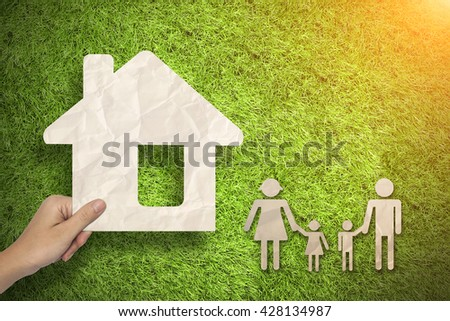 Hand hold House and family concept on green grass background
