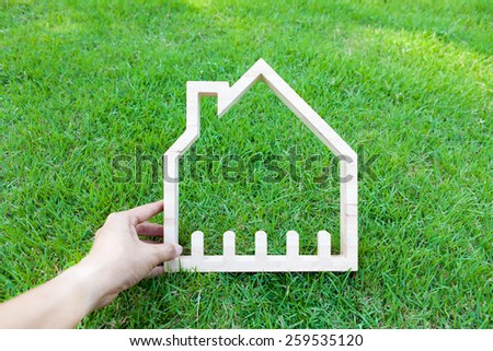 Hand hold house on green field, house icon concept
