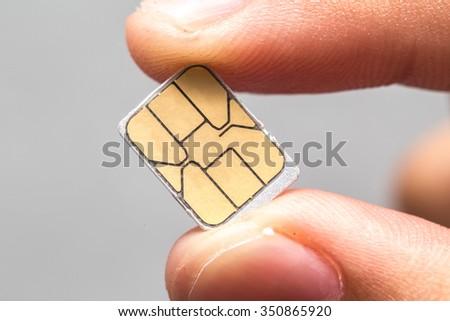 Hand hold micro nano SIM card isolated - stock photo
