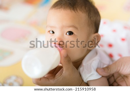 Hand hold milk bottle for feeding asian baby girl