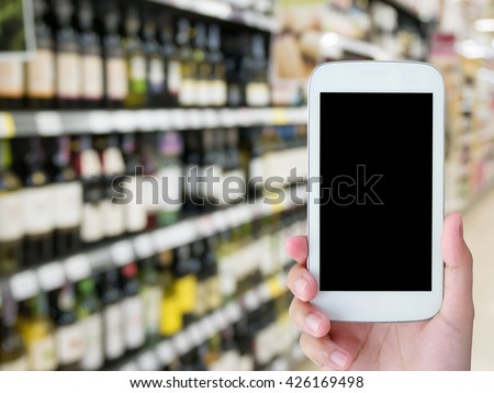 hand hold mobile smartphone with blur wine bottles on shelf in wine store - stock photo