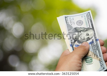 hand hold one hundred dollar bill over blur tree background - stock photo