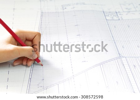hand hold pencil. over blurred architectural blueprint of office building - stock photo