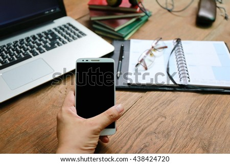 hand hold phone on wood table with laptop and book - stock photo