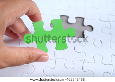 Hand hold piece of color puzzle over white puzzle, copy space.