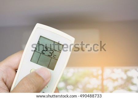 Hand hold remote control with conditioner background