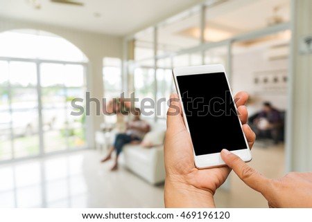 hand hold smart phone over blurred image of coffee shop or modern living room