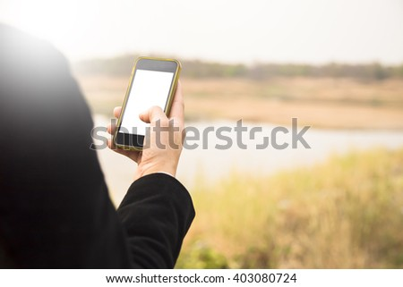 Hand hold smart phone with mountain and water view - stock photo