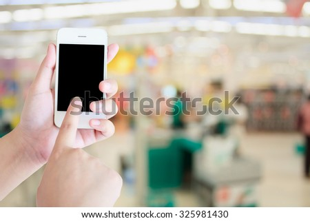 hand hold smartphone with Supermarket store background ,Cashier counter with customer - stock photo