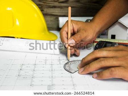 hand hold stationery. over blurred architectural blueprint of office building - stock photo