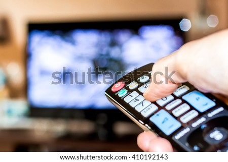 Hand hold the remote control to change channels on Television