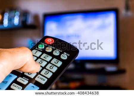 Hand hold the remote control to change channels on Tv - stock photo