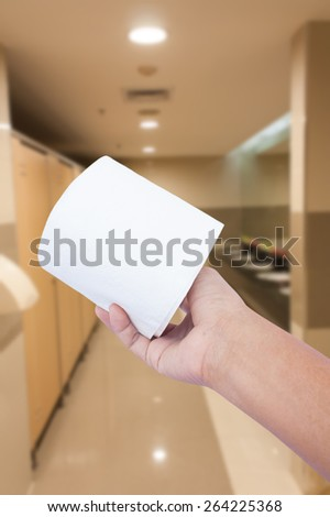 hand hold toilet paper in toilet background  - stock photo