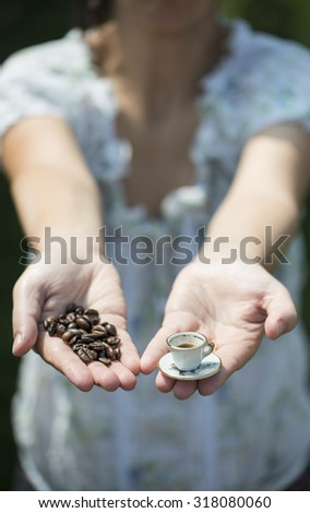 Hand hold very small cup of coffee. Miniature cup
