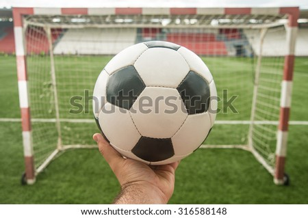 Hand hold white and black leather ball in fingers against green grass football field and gate with nett Soccer goalkeeper trying to defend on sport stadium with seat background  - stock photo