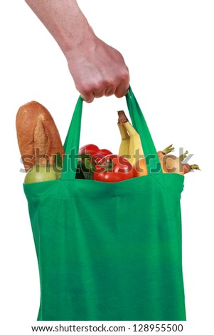 Hand holding a bag filled with groceries, isolated on white - stock photo