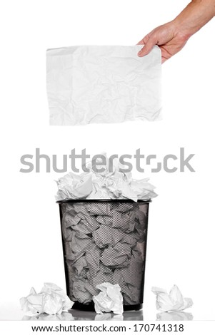 Hand holding a battered card over the trash can - stock photo
