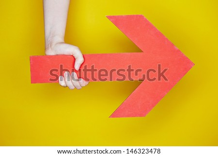Hand holding a big red arrow pointing to the right - stock photo