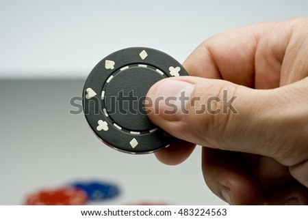 Hand holding a black playing chip.
