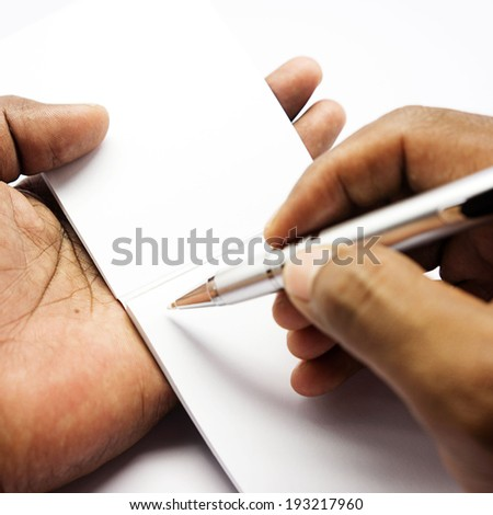 hand holding a book and pen - stock photo