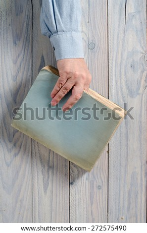Hand holding a book. Wooden background