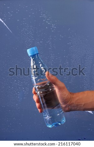 hand holding a bottle of water on blue - stock photo