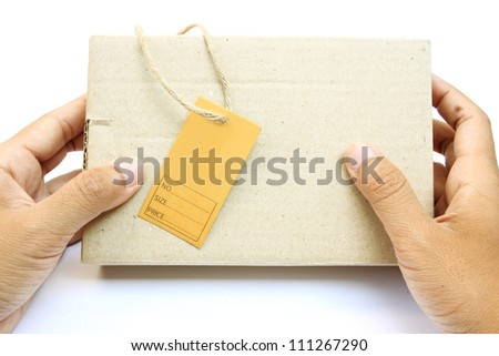 Hand holding a box with brown empty paper tag on white background - stock photo