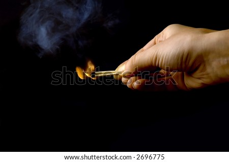 hand holding a burning match, isolated on black background