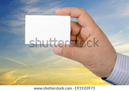 Hand holding a business card on background a beautiful sunset sky