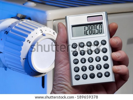 Hand holding a calculator in front of a radiator. - stock photo
