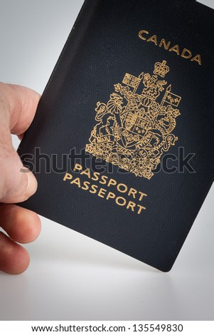 Hand holding a Canadian passport on a grey background - stock photo