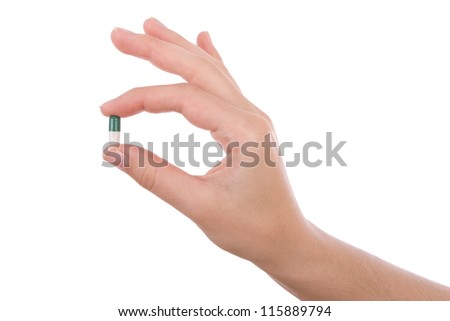 Hand holding a capsule or pill isolated on white - stock photo