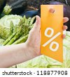 hand holding a card for discounts against products in the store - stock photo