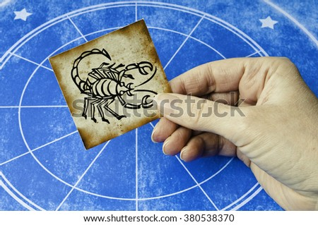 hand holding a card with sign of scorpion - stock photo