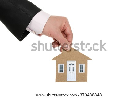 hand holding a cardboard house with real door and windows isolated on white - stock photo
